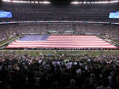 A large American flag covers the field during the playing of the national anthem before the game between the New York Jets and the Dallas Cowboys at MetLife Stadium in New York