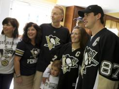 Pittsburgh Penguins captain Sidney Crosby  poses for a photo after delivering season tickets to Annette and Gary Hensler at their home.