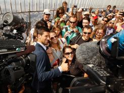 Novak Djokovic is the center of attention on the observation deck at the Empire State Building.