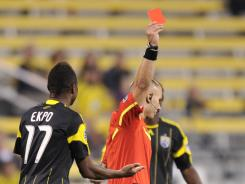 Columbus Crew's Emmanuel Ekpo is given a red card in the 11th minute of an eventual 2-2 draw with the Houston Dynamo.