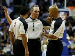 From left to right, NBA referees Bill Kennedy, Joe DeRosa and Marc Davis talk in a huddle during a 2010 playoff game in Orlando. The referees and the league have agreed to a new deal.
