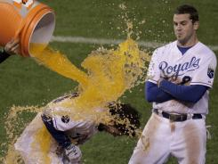 The Royals' Eric Hosmer, who drove in the game-winning run, gets doused by teammates as Mike Moustakas, right, looks on after Kansas City's win over Chicago.