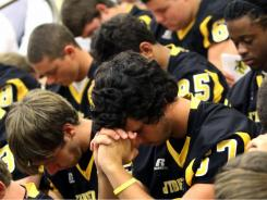 "Members of the D'Iberville High football team pray during a memorial service for for teammate Latrell ""Fred"" Dunbar at the school on Thursday."