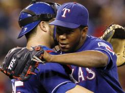 Texas Rangers closer Neftali Feliz gets a hug from catcher Mike Napoli after the team defeated the Seattle Mariners 7-6 Saturday night.