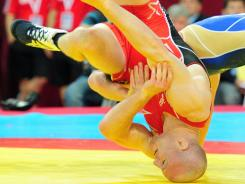 Cael Sanderson, wearing red, fell to Russia's Albert Saritov in the bronze medal match in the 185-pound class at the Senior Wrestling World Championship in Istanbul on Saturday. He ended up placing fifth.