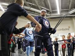 Young fans welcome Zach Bogosian and the Winnipeg Jets as they head to the ice during  training camp in Winnipeg