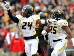 West Virginia defensive back Eain Smith (24) celebrates after his interception late in the fourth quarter clinched a win by the Mountaineers.