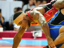 Jordan Burroughs, left,  of  the USA  wrestles with Iran's Sadegh Saeed Goudarzi (in blue) during the 74kg freestyle gold medal match at the Senior Wrestling World Championship.