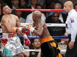 Floyd Mayweather delivers a fourth-round knockout punch to Victor Ortiz as referee Joe Cortez watches Saturday night in Las Vegas.