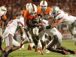 Miami running back Mike James breaks through the Ohio State defense for yards during the second half.