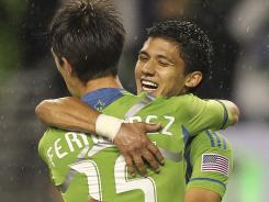 Fredy Montero, facing, celebrates with Seattle Sounders teammate Alvaro Fernandez after a 3-0 thrashing of D.C. United.