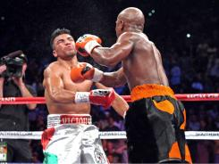 Victor Ortiz, left, falls towards the canvas after being hit with a right from Floyd Mayweather in the fourth round, ending the fight. Mayweather controversially knocked out Ortiz to win the WBC Welterweight title.