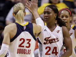 Fever players Katie Douglas, left, and Tamika Catchings high five after a play late in the second half of a WNBA first round playoff basketball game against the New York Liberty in Indianapolis on Monday.