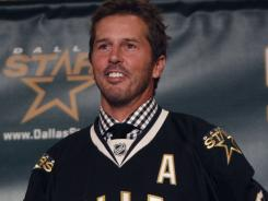 Mike Modano wears a Dallas jersey during a news conference Friday announcing his retirement from the NHL. Modano signed a one-day contract with the team so he could retire as a Star.