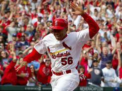 Rookie pinch runner Adron Chambers (56) scampers home with the game-winning run for the Cardinals.