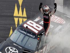 Kyle Busch gestures to the crowd after winning at New Hampshire Motor Speedway on Saturday. It was his 18th victory between Sprint Cup, Nationwide and Trucks this season.