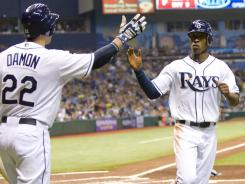 Johnny Damon, left, who drove in four runs for the Rays, congratulates B.J. Upton after the latter scored a run in Saturday's win over the Blue Jays.