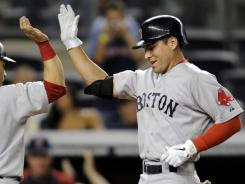 The Boston Red Sox's Jacoby Ellsbury, right high-fives with Marco Scutaro after Ellsbury hit a three-run home run against the Yankees during the 14th inning at Yankee Stadium in the Bronx.