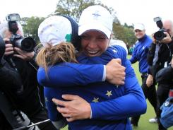 Suzann Pettersen hugs teammate Azahara Munoz after Europe defeated the USA to capture the Solheim Cup on Sunday in Dunsany, Ireland.