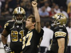 Former Saint Steve Gleason acknowledges the crowd Sunday flanked by DE Will Smith (91) and QB Drew Brees.