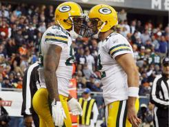 Packers TE Jermichael Finley, left, celebrates one of his three TD hook-ups with QB Aaron Rodgers on Sunday in Chicago.