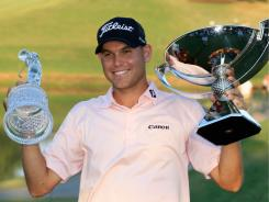 Bill Haas holds up both trophies, for the Tour Championship and the FedExCup, after his victory Sunday in Atlanta.