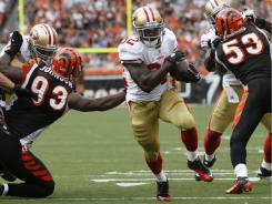 San Francisco 49ers running back Kendall Hunter runs for a seven-yard touchdown past Cincinnati Bengals defensive end Michael Johnson (93) and linebacker Thomas Howard (53).