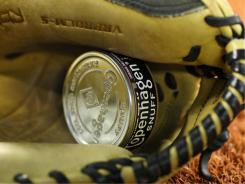 A tin can of chewing tobacco rests in a glove before the Boston Red Sox game against the Toronto Blue Jays.
