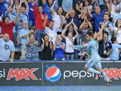 Midfielder Omar Bravo  of Sporting Kansas City runs past cheering fans after scoring on a penalty kick in the 92nd minute against the Los Angeles Galaxy on Sept. 5,  at Livestrong  Sporting Park in Kansas City, Kan.