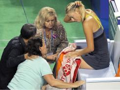 Maria Sharapova of Russia receives treatment after injuring her left ankle in her match against Petra Kvitova.