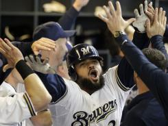 Prince Fielder is congratulated in the dugout after hitting a two-run home run during the seventh inning to give the Brewers a 4-0 lead.