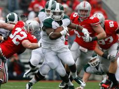 Michigan State's Le'Veon Bell find running room against the defense of Ohio State.