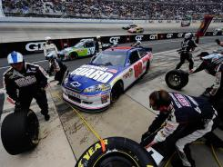 Crew members change the tires on Dale Earnhardt Jr's car during Sunday's AAA 400 at Dover International Speedway.