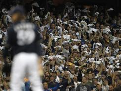 Brewers fans, seen here cheering on closer John Axford to finish a Game 2 win over the Diamondbacks on Sunday, may be excited about their team in the playoffs but more local viewers watched the Packers win.