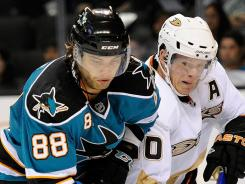 Brent Burns, left, and reigning MVP Corey Perry battle for the puck in a preseason game.