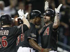 Diamondbacks' Ryan Roberts, right, is greeted at the plate by teammates following his first-inning grand slam against the Brewers.