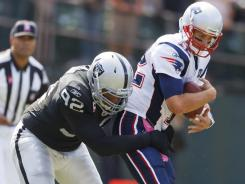 New England Patriots quarterback Tom Brady (12) is tackled by Oakland Raiders defensive tackle Richard Seymour on a dead play during their game in Oakland.