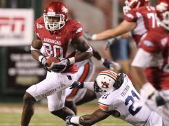 Arkansas tight end Chris Gragg runs after a catch as Auburn linebacker Eltoro Freeman tries to make a tackle.
