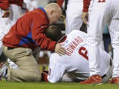 Trainers and coaches surround Ryan Howard after the slugger was hurt on a groundout to end the Phillies' season.