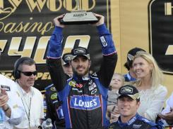 Jimmie Johnson hoists the victory trophy after his dominant performance at Kansas Speedway.