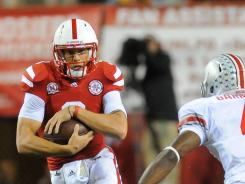 Quarterback Taylor Martinez looks to avoid Ohio State defensive back C.J. Barnett during their game at Memorial Stadium in Lincoln, Neb. Martinez threw for two touchdowns and ran for another score in the biggest comeback in Nebraska history.