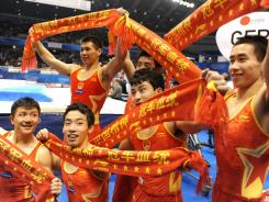 Chinese gymnasts celebrate their victory in the men's team event final at the World Gymnastics Championships in Tokyo on Wednesday.