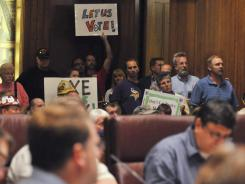 Audience members hold signs as the Ramsey County Charter Commission meets before a packed house  in St. Paul Tuesday to discuss a proposal to build a $1 billion, taxpayer-supported  football stadium in suburban Arden Hills.