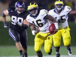 Michigan Wolverines quarterback Denard Robinson (16) runs with the ball in the second half against the Northwestern Wildcats at Ryan Field.