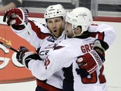 Dennis Wideman, left, and Mike Green celebrate the former's game-winning overtime goal.
