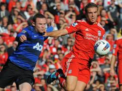 Liverpool's Jordan Henderson holds off Manchester United's Wayne Rooney during a match Saturday in Liverpool.