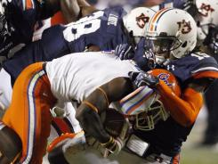 Neiko Thorpe leads an Auburn that tackles Florida running back Chris Rainey during the second half.