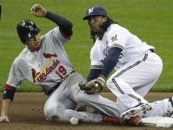 Brewers second baseman Rickie Weeks can't handle the throw as Jon Jay steals second base during the Cardinals' four-run first inning.