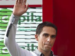Spanish cyclist Alberto Contador waves on the podium after the 13th stage of the Tour of Spain, on Sept. 2, 2011.