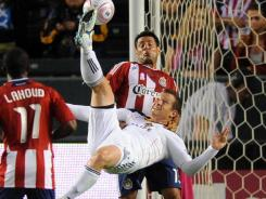 Los Angeles Galaxy forward Chad Barrett  hits a bicycle kick as he is defended by Chivas USA's Ante Jazic.